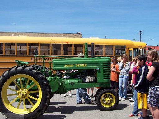 group of school kids staring at a John Deer tractor