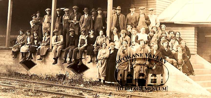 Workers sitting outside of the Opportunity Fruit Processors. Image is pre 1920s